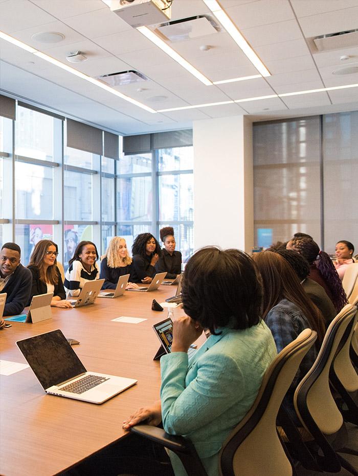 grupo de personas sentadas en mesa de sala de reuniones